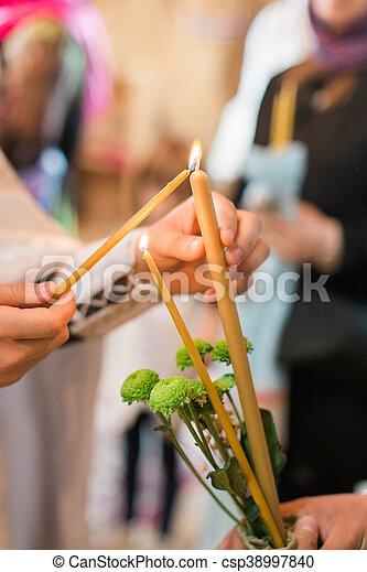 burning thin candle during christening Orthodox baptism - csp38997840