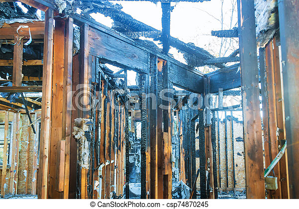 Burnt black house after fire damaged interior details arson from a home - csp74870245