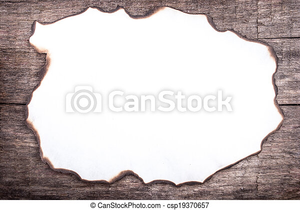 burnt paper on wood, can be used as a background or a frame for text - csp19370657