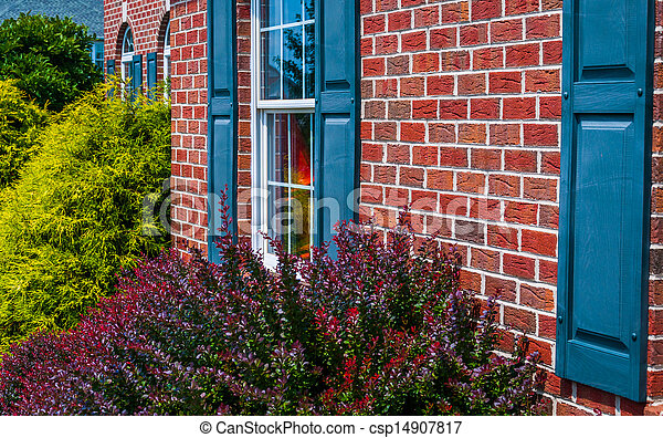Bushes and front of brick house with blue shutters - csp14907817
