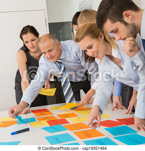 Business Colleagues Arranging Labels On Table - csp19351464