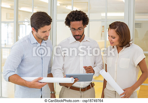 Business colleagues using digital tablet with blueprints - csp18749764
