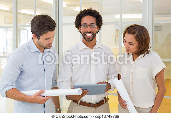 Business colleagues using digital tablet with blueprints - csp18749769