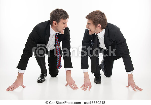 Business competition. Two angry young business people standing at the start line and looking at each other while isolated on white - csp16550218