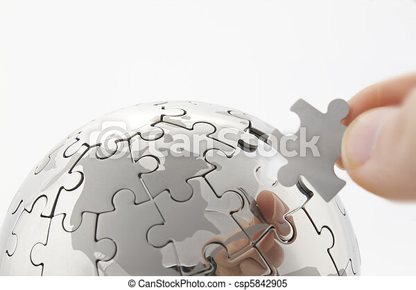 business concept with a hand building puzzle globe on white, space for messages - csp5842905