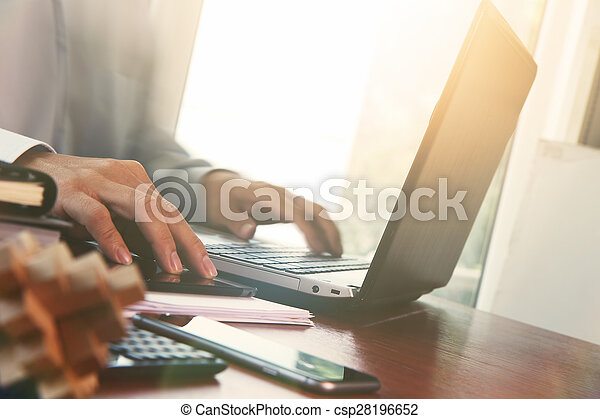 business documents on office table with digital tablet and man working with smart laptop computer background  - csp28196652