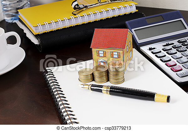 business fountain pen with coins stack and paper house and calculator on wooden desk table - csp33779213