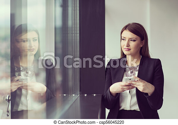 Business Girl Standing In A Modern Building Near The Window With Phone - csp56045220