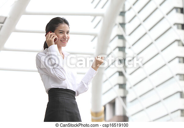 Business lady answering the phone with a smile, receiving good news  - csp16519100