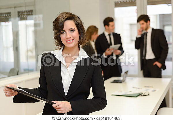 Business leader looking at camera in working environment  - csp19104463