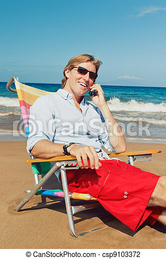 Business man calling by cell phone at the beach - csp9103372