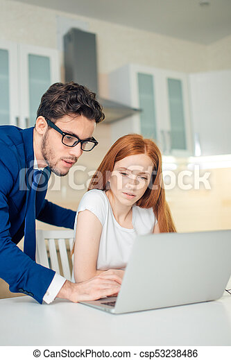 Business man explaining something to woman with laptop - csp53238486
