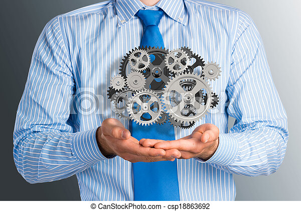 business man holds up a mechanism of gears - csp18863692