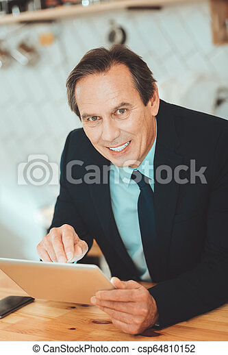 Business man sitting with tablet - csp64810152