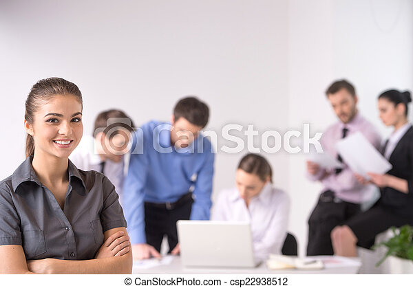 Business meeting - manager discussing work with his colleagues. woman standing on foreground with crossed hands and team on background - csp22938512