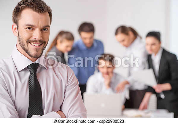 Business meeting - manager discussing work with his colleagues. closeup on man standing on foreground with crossed hands and team on background - csp22938523