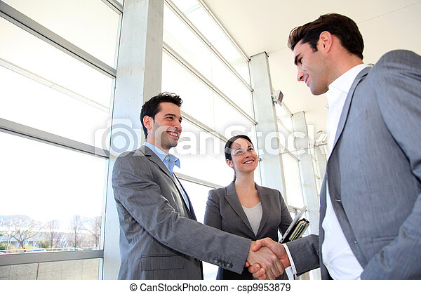Business partners shaking hands in meeting hall - csp9953879
