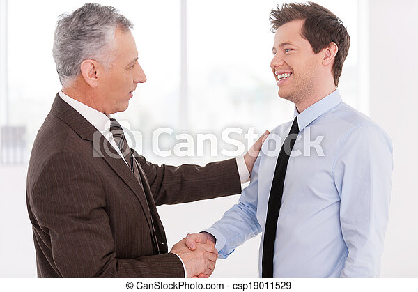 Business partners. Two cheerful business men shaking hands and looking at each other - csp19011529