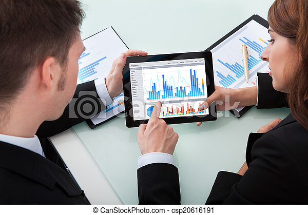 Business People Discussing Over Graphs On Digital Tablet - csp20616191
