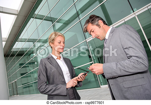 Business people exchanging phone numbers - csp9977601