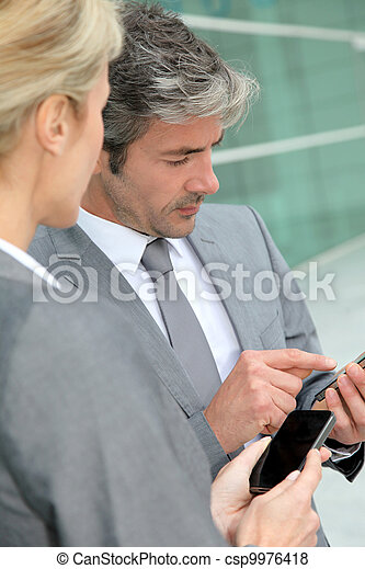 Business people exchanging phone numbers - csp9976418
