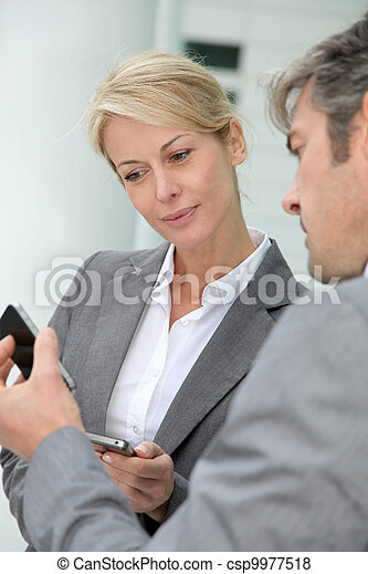 Business people exchanging phone numbers - csp9977518