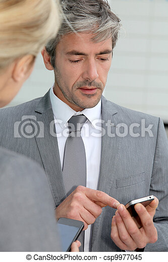 Business people exchanging phone numbers - csp9977045