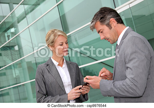 Business people exchanging phone numbers - csp9976544