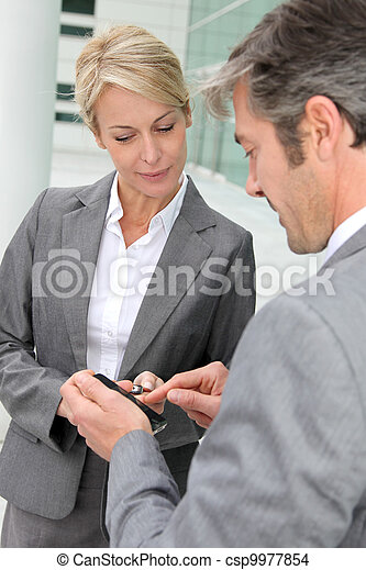 Business people exchanging phone numbers - csp9977854