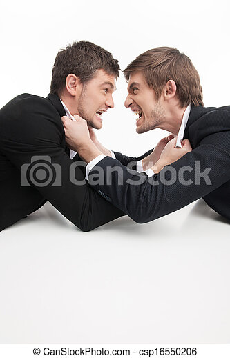 Business people fighting. Two angry young business people fighting while isolated on white - csp16550206