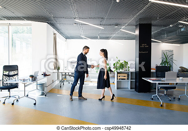 Business people in the office. Man and woman shaking hands. - csp49948742