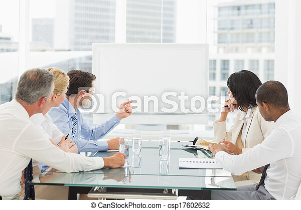 Business people looking at blank whiteboard in conference room - csp17602632