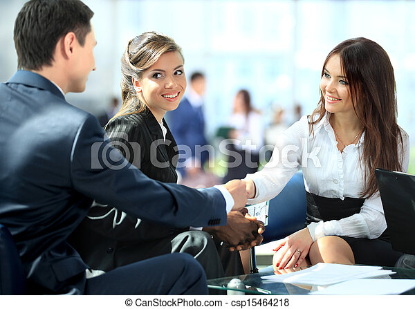 Business people shaking hands, finishing up a meeting - csp15464218