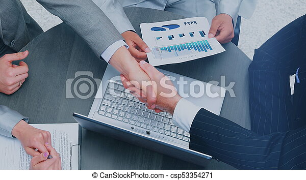 Business people shaking hands, finishing up a meeting - csp53354271