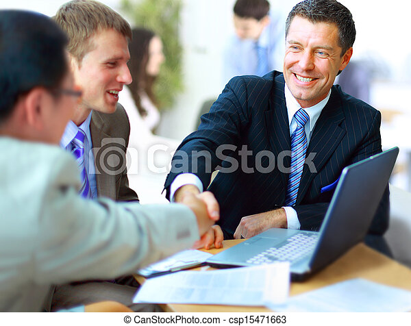 Business people shaking hands, finishing up a meeting  - csp15471663