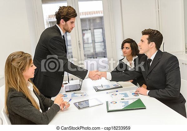 Business people shaking hands, finishing up a meeting  - csp18233959