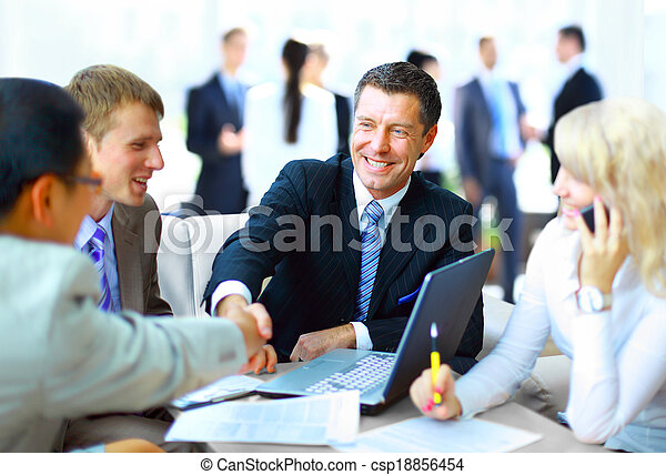Business people shaking hands, finishing up a meeting  - csp18856454