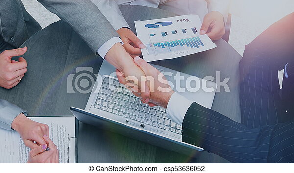 Business people shaking hands, finishing up a meeting - csp53636052