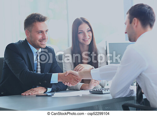 Business people shaking hands, finishing up a meeting - csp52299104
