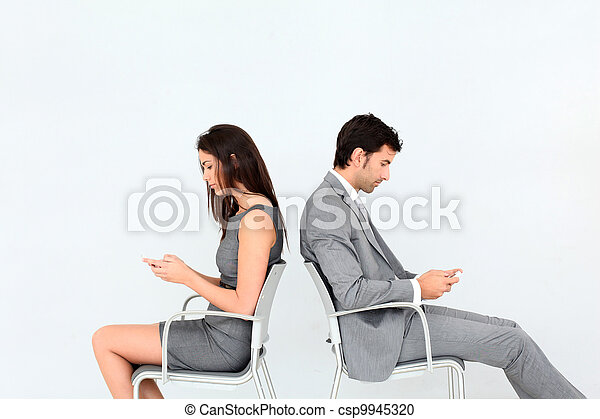 Business people sitting in chairs with mobile phone - csp9945320