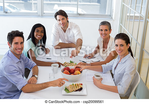 Business people smiling at camera eating sandwiches and fruit for lunch in the office - csp20099561