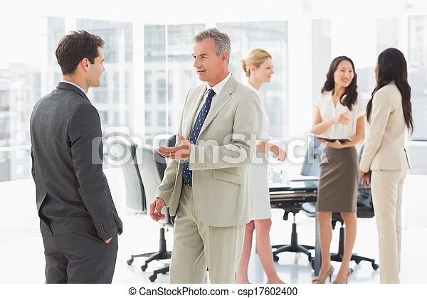 Business people speaking together in conference room - csp17602400