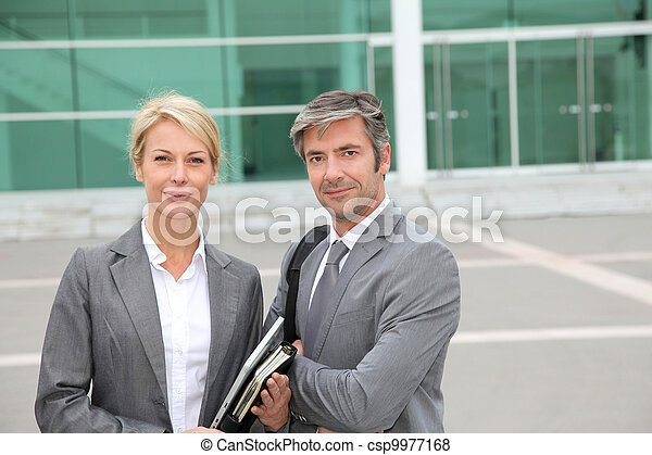 Business people standing in front of exhibition building - csp9977168
