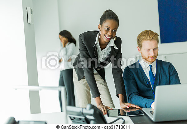 Business people talking and smiling in an office in front of a laptop - csp31713011