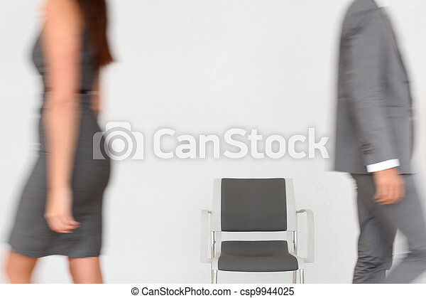 Business people walking by chair set in hallway - csp9944025
