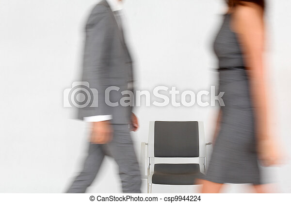 Business people walking by chair set in hallway - csp9944224