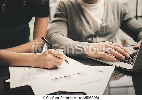 Business situation, signs contracts. Closeup photo finance manager working modern office with new business project. Using laptop,startup idea,team work. Horizontal. Blurred background,film effect - csp35963963