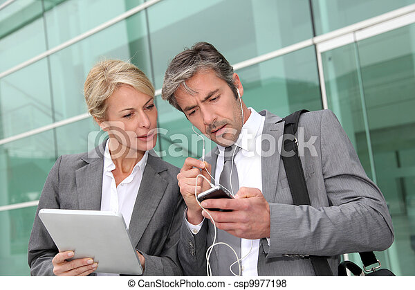 Business team meeting outside with tablet - csp9977198