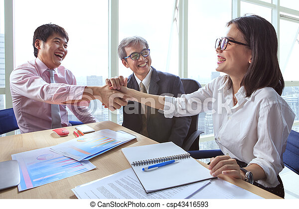 business team shaking hand and laughing happiness for successful working project - csp43416593