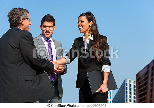 Business team shaking hands over deal outdoors. - csp9608908